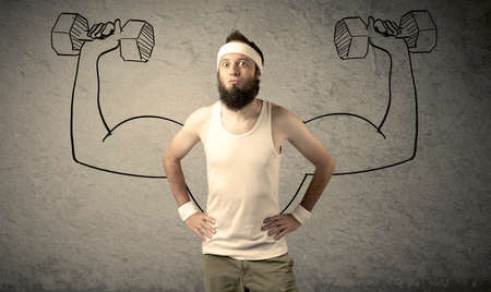 A young college student with beard and glasses posing in front of grey background, thinking about lifting weight with big muscles, illustrated by white drawing concept. photo