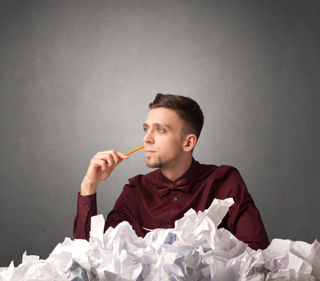 preference: Young businessman sitting behind crumpled paper with grey background Stock Photo