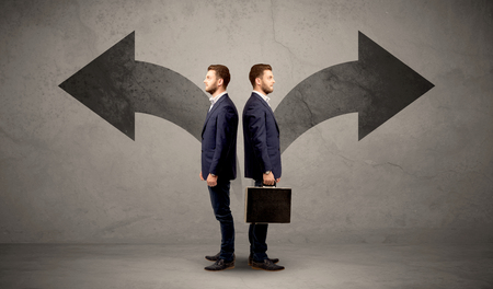 contradiction: Young conflicted businessman choosing between two directions represented by black arrows