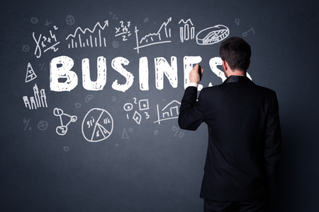 Young businessman in black suit standing in front of a detailed business plan photo