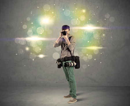 A young amateur photographer with professional camera equipment taking picture in front of grey wall full of colorful bokeh and glowing lights concept photo