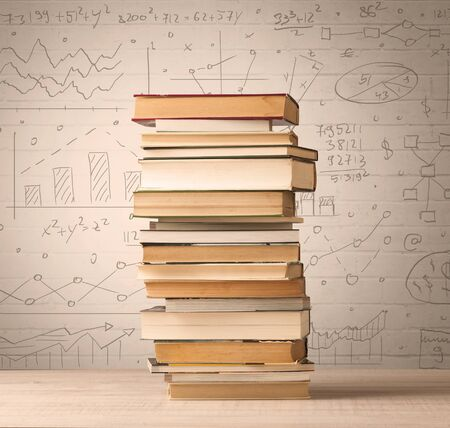 school class: A pile of books with math formulas written in doodle style on background Stock Photo