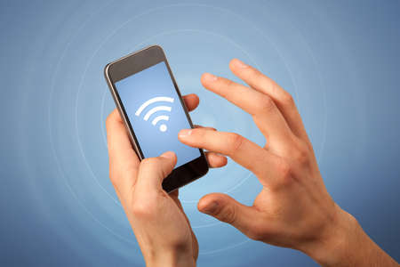 wireless communication: Female fingers touching smartphone with wireless connection icon