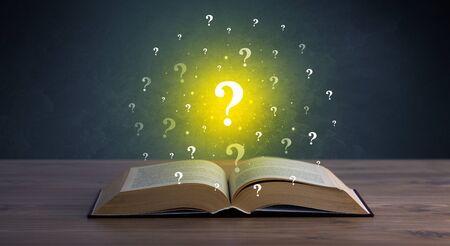 marca libros: signos de interrogación amarillo flotando sobre el libro abierto