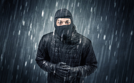 Burglar in action in black clothes with rainy concept. Stock Photo