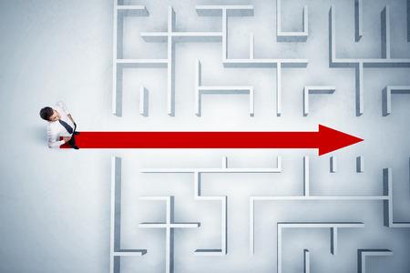 ビジネスの男性のパスを示す赤い矢印で迷路を見て