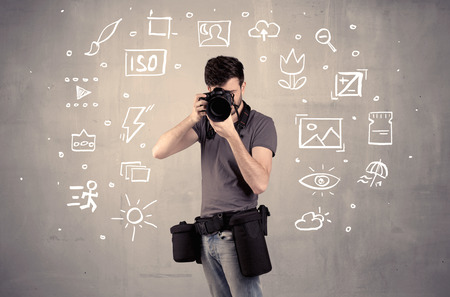 An amateur hobby photographer learning to use a professional digital camera with camera settings icons on the background wall concept photo