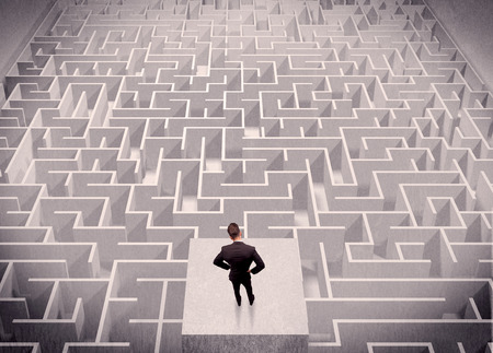 A confused businessman thinking while standing on a square platform above a detailed maze photo
