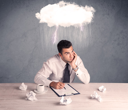 An elegant office worker is having a bad day while working, illustrated by a white cloud above his head with heavy rain and thunder concept photo