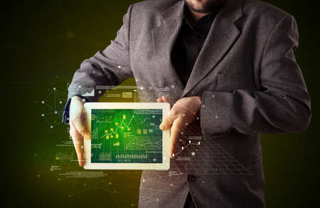 Casual businessman holding tablet with strategy and business related graphics