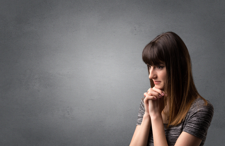 Young woman praying on a grey background