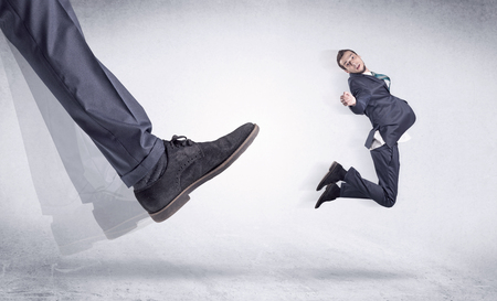 mobbing: Boss mobbing his worker, illustrated by black shoe kicking small businessman who is flying away in the space