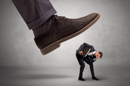 Employee is afraid of the big boss foot, which is stepping down him Stock Photo