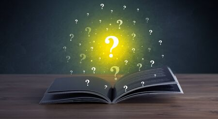 Yellow question marks hovering over open book Stock Photo