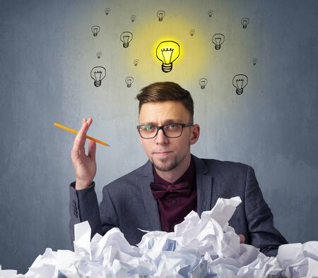 preference: Young businessman sitting behind crumpled paper with lightbulbs above his head