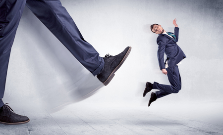 small world: Giant leg kicking small businessman and he is flying away