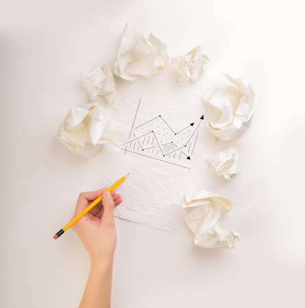 Female hand next to a few crumpled paper balls drawing a progress chart Stock Photo