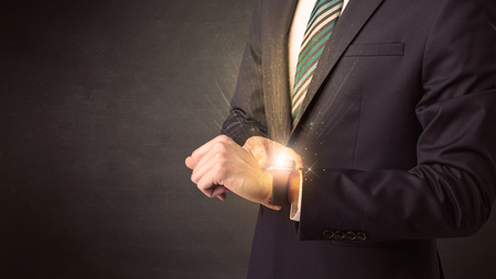 storage: Businessman wearing smartwatch with shiny rays on it.