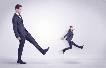 flit: Big man in suit kicking out little himself out with simple white wallpaper Stock Photo
