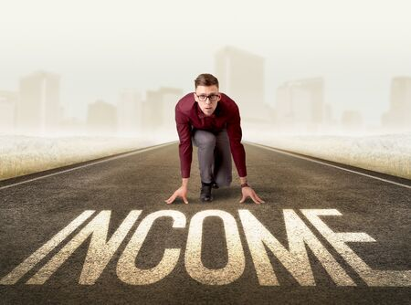 Young determined businessman kneeling before income sign Stock Photo