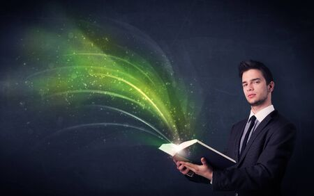 aura energy: Casual young man holding book with green wave flying out of it