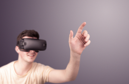 electronic background: Young impressed man wearing virtual reality goggles