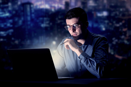 Young handsome businessman working late at night in the office with blue lights in the background Stock Photo