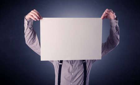 Young businessman hiding behind a blank piece of paper