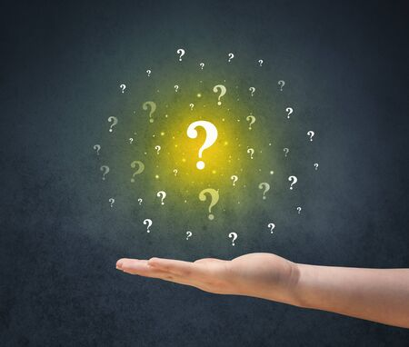 indecisive: Yellow question marks hovering over young hand