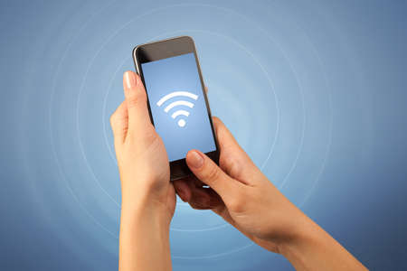 electronic background: Female fingers touching smartphone with wireless connection icon