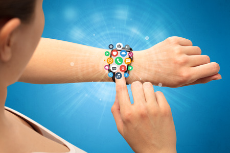 electronic background: Hand with smartwatch and application symbols nearby.