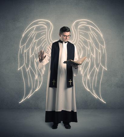 Un sacerdote varón joven con grandes alas de ángel extraídas de pie con la Santa Biblia en su concepto de manos. Foto de archivo - 87048825