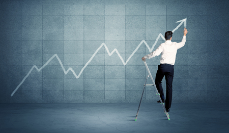 human evolution: A man standing on a ladder and drawing a chart on blue wall background with exponential progressing curve, line