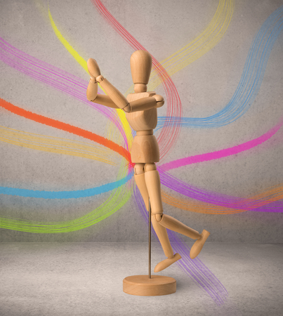 puppets: Wooden mannequin posed in front of a greyish background with colorful lines behind it