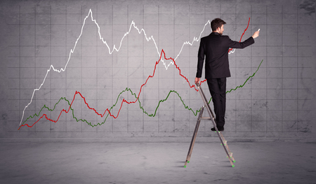 human evolution: A guy in modern suit standing on a small ladder and drawing a chart on grey wall background with exponential progressing curves, lines