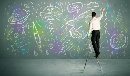 human evolution: A talented student drawing rockets, planets on extraterrestrial life from a small ladder