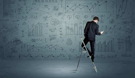 human evolution: A businessman in modern stylish elegant suit standing on a small ladder and drawing pie and block charts on grey wall background with exponential progressing curves, lines, circles, angles, blocks, numbers Stock Photo