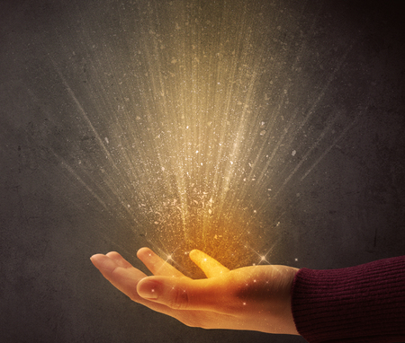aura energy: Yellow ray of light coming from a young hand