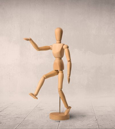 puppets: Wooden mannequin posed in front of a greyish background Stock Photo