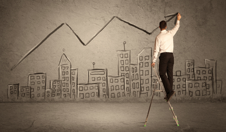 human evolution: A man in elegant suit standing on a small ladder and drawing a line on brown wall background with buildings Stock Photo