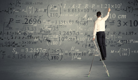 human evolution: A businessman in elegant suit standing on a small ladder and writing numbers, calculating on grey wall background