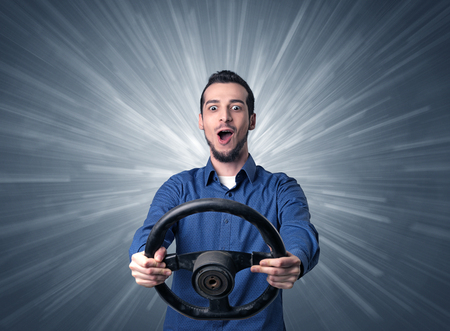 Young man holding black steering wheel with white lines behind him