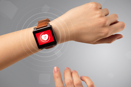 Naked female hand with smartwatch and with heart rate icon on the watch