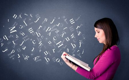 education concept: Casual young woman holding book with white letters flying out of it Stock Photo