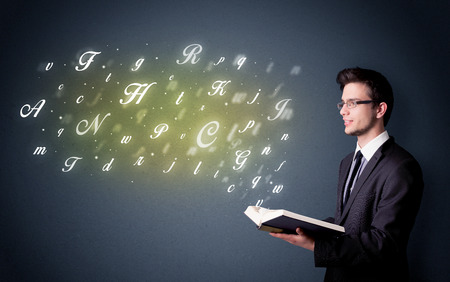 education concept: Casual young man holding book with shiny letters flying out of it