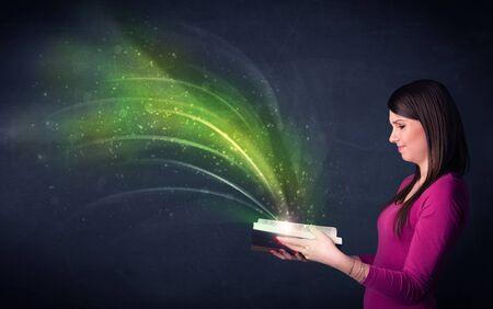 aura energy: Casual young woman holding book with green wave flying out of it