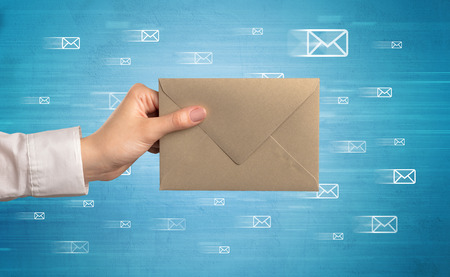 Female hand holding coloured and white envelope with blue background and message symbols around Reklamní fotografie