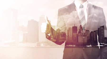 Businessman standing at cityscape background with warm light Stock Photo