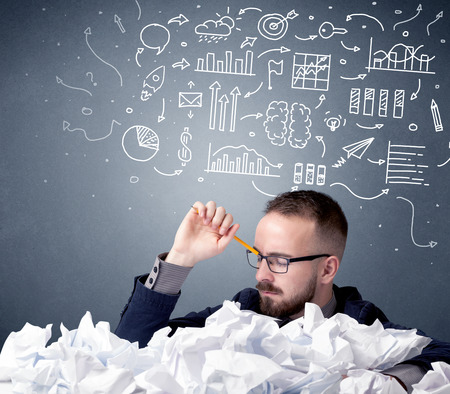 Young businessman sitting behind crumpled paper with mixed drawings over his head