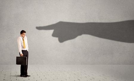 事業者概念の背景に彼を指している巨大な影の手を見て 写真素材